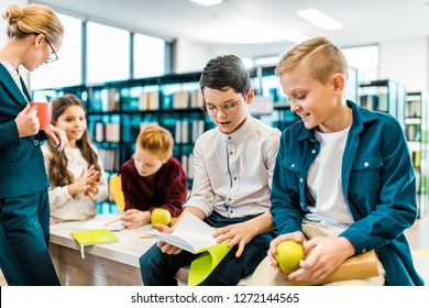 young female librarian looking at kids reading books in library