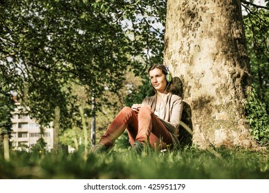 Young female listen music seated at the park