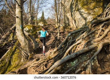 young female with long hair running over roots on hard trail with rocks in the spring