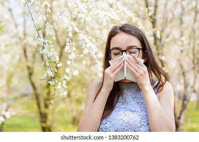 Young female with long natural hair in light blouse sneezing because of bloom pollen from trees in spring. Concept of allergy on pollen