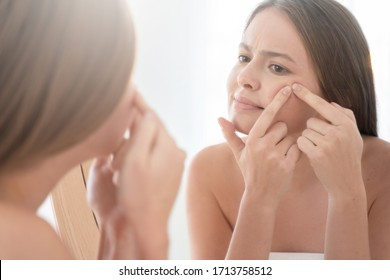 Young female looking in bathroom mirror, trying desperately to squeeze pimple on her cheek, feeling annoyed because of problems with skin