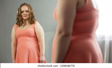 Young female looking in mirror with disgust, ashamed of fat body, obesity issue