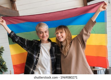 Young female love lesbian couple stretching holding showing LGBT rainbow flag showing their support for equal rights for sexual minorities and freedom of love
