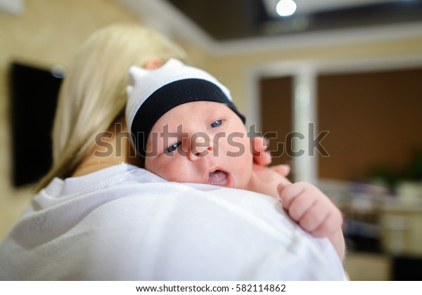 Young female lulls and sings songs for child, gently hugging and talking with kid, baby located in mother's arms in room. Woman blonde European appearance dressed in white T-shirt, newborn baby