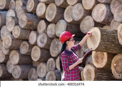 Young female lumber engineer standing beside cut logs and writing notes