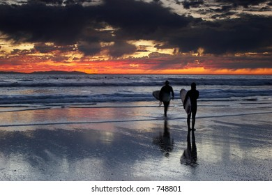 Young female and male surfers on the beach at sunset.