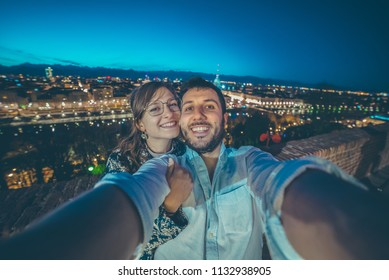 Young female and man couple tourist standing on the famous cityscape with Mole Antonelliana in Turin (torino) city. Travelling in Europe, Piedmont region in Italy