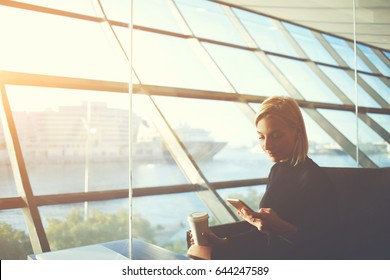 Young female managing director is reading e-mail on mobile phone, while is waiting her fly in international airport hall.Woman lawyer with take away coffee is watching financial news on cell telephone