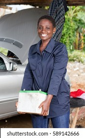 Young female mechanic raises a car battery to place it in the engine of this car.