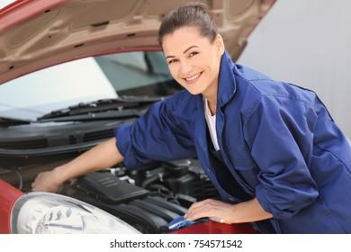 Young female mechanic repairing car outdoors