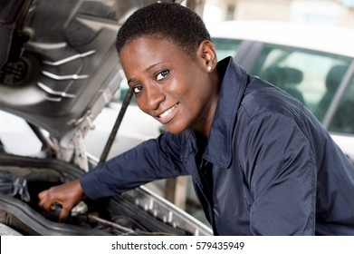 Young female mechanic repairs a car by putting the engine in good condition.