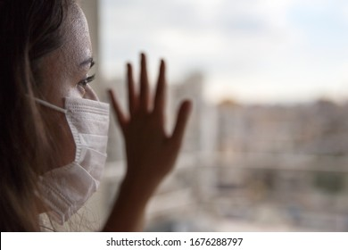 Young female in a medical protective mask looks out the window