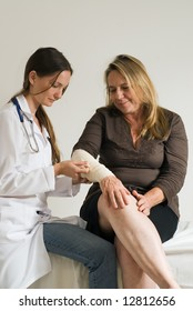 Young female medical student bandaging a middle-aged woman's right arm.