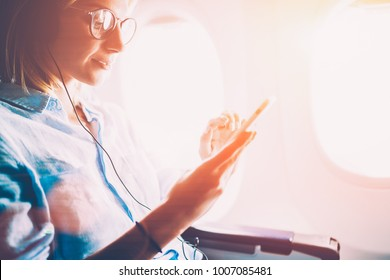 Young female meloman listening favorite songs during flight in first class cabin using mobile playlist and accessory, woman entertaining on airplane board enjoying music in headphones from smartphone