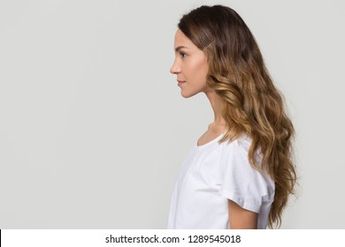 Young female millennial woman standing in profile on white grey background with copy free space for text, confident serious girl lady model isolated on blank studio wall, side view portrait