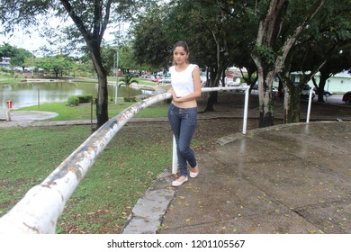 Young female model with casual clothing next to iron bar in square, with trees and lake in the background