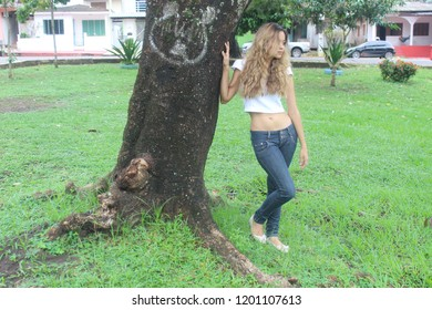 Young female model with casual clothing next a tree in public square