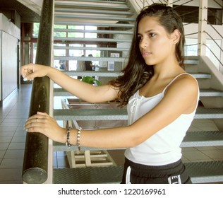 Young female model, with casual clothing, resting on a stair railing