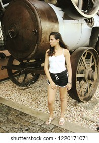 Young female model with casual clothing next to a train