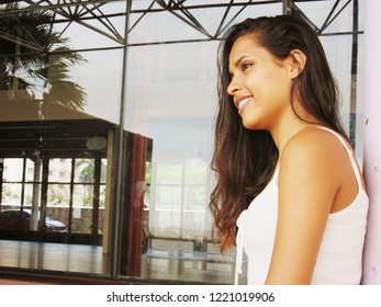 Young female model, with casual clothing, smiling, leaning against a column, in a sunny day