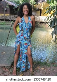Young female model with colorful dress smiling with watercourse in the background
