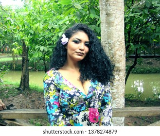 Young female model with colorful dress and flower in hair next a tree