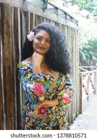 Young female model with colorful dress and flower in hair next to a wooden fence