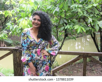 Young female model with colorful dress near a cacaotree