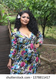Young female model with colorful dress and flower in hair next to a wooden walkway