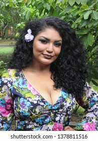 Young female model with colorful dress and flower in hair