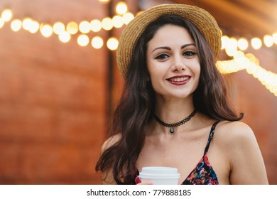 Young female model with dark long hair, hazel eyes and red lips, wearing necklace, summer hat and dress having delightful expression while posing at outdoor cafe. People, rest, emotions concept