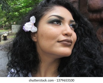 Young female model with flower in curly hair