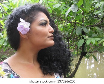 Young female model with flower in hair near a cacaotree with green fruit