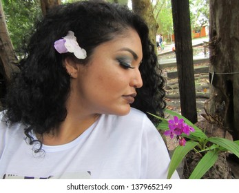 Young female model with flower in hair seeing a flower