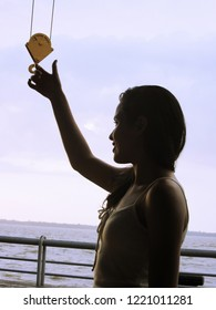 Young female model with the hand next to a hook suspended by two cords