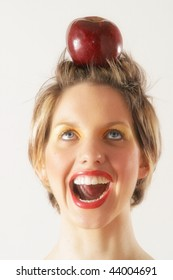 A young female model holds apple on her head like a target