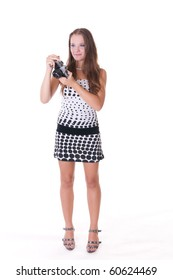 Young female model in polka dot dress posing with 35mm camera, isolated on white