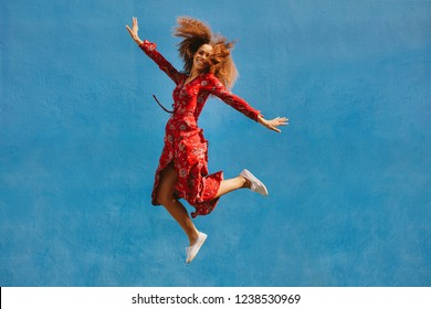 Young female model in red sundress jumping with joy. Beautiful young woman jumping over blue background.