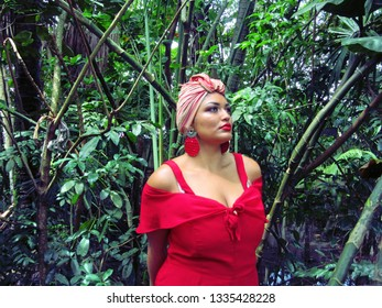 Young female model with turban and red clothing in park