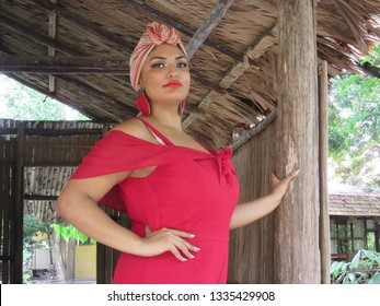 Young female model with turban and red clothing at the entrance of the wooden house