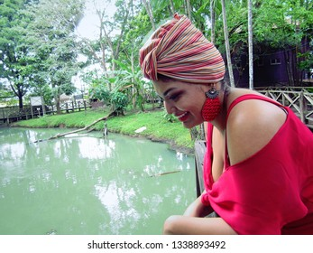 Young female model with turban and red clothing near a wooden fence in park, next to a waterway