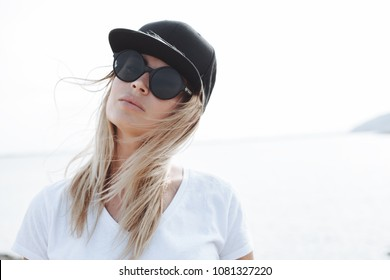 Young female model wearing black cap and sunglasses. Outdoors lifestyle portrait