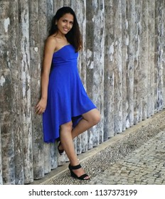 Young female model, wearing a blue dress, poses in front of a wall of logs