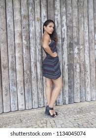 Young female model, wearing a dress, poses in front of a wall of logs