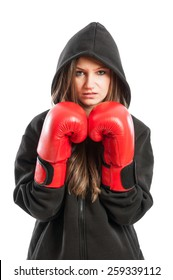 Young female model wearing red boxing gloves and black hoodie isolated on white background