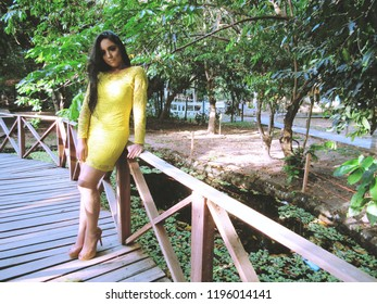 Young female model with yellow dress on walkway over lake of urban park