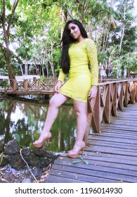 Young female model with yellow dress near a walkway over lake of urban park