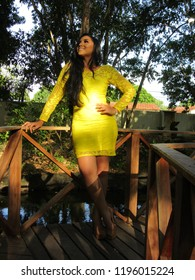 Young female model with yellow dress on walkway over lake in urban park, shaded by trees