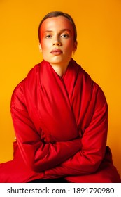 Young female modern wrapping in warm oversize red coat and looking at camera against yellow background