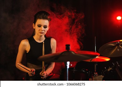 Young female musician playing drums